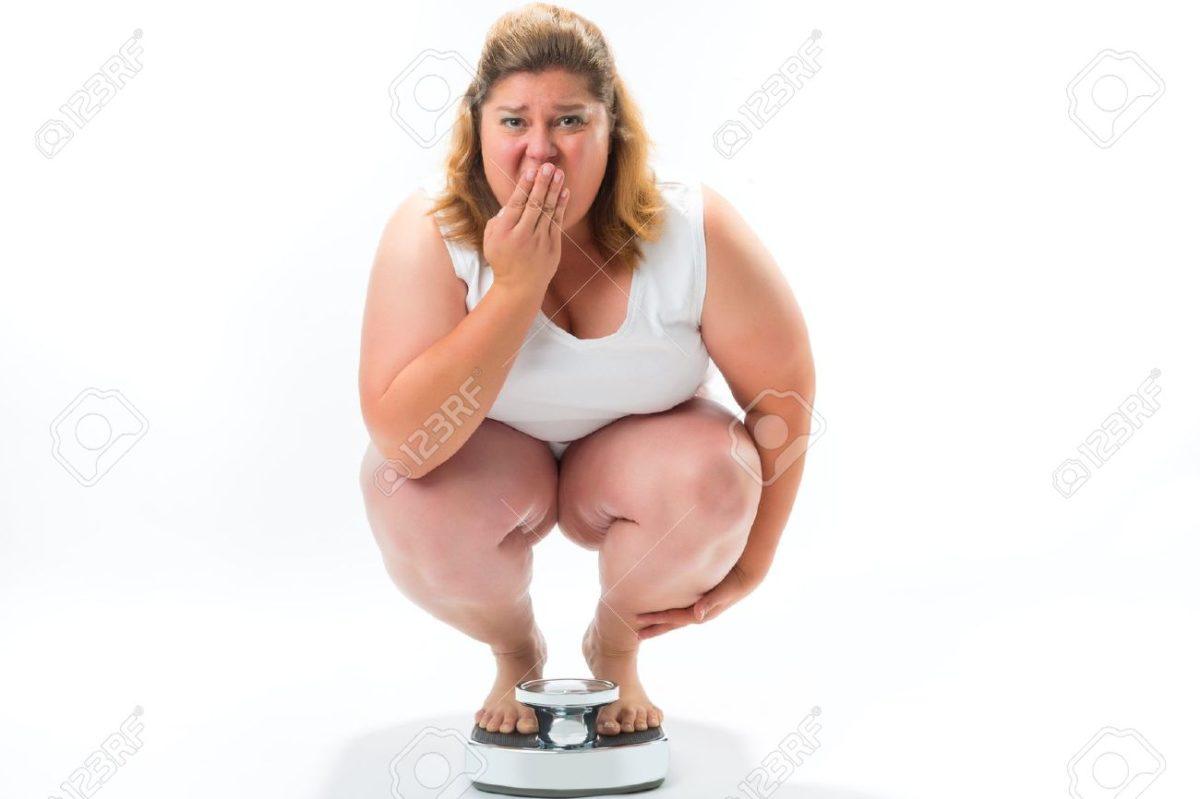 17657362-La-dieta-y-el-peso-la-mujer-obesa-joven-agachado-en-una-escala-que-mide-su-peso-Foto-de-archivo